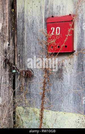 Old rural wooden entrance door of an abandoned Bulgarian village house with a red letter box with the number twenty - Stock Photo