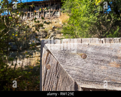 Part of an old wooden gate in the foreground, blurred old wooden barn on a rocky hill in the background, at the Fore-Balkan village of Debnevo, Bulgar - Stock Photo