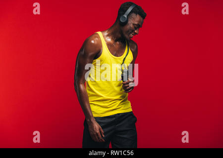 African muscular man with jumping rope listening to music on headphones on red background. Fit young man relaxing after workout. - Stock Photo