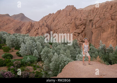 A female tourist poses for a photograph in front of the Atlas Mountain range, Ouzazate, Dades Gorge - Stock Photo