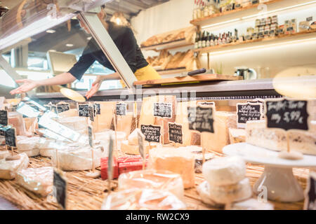 Shop clerk woman sorting cheese in the supermarket display - Stock Photo
