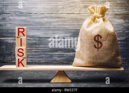 Money bag and wooden blocks with the word Risk. The concept of financial risk. Justified risks. Investing in a business project. Making the right deci - Stock Photo