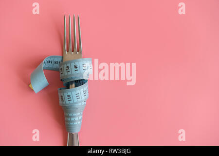 fork wrapped in tape measure on pink background. Proper nutrition. Medical starvation. Diet for weight loss concept. Free space for text. - Stock Photo