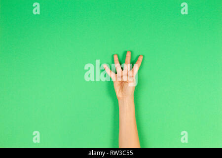 Kid hand showing four fingers on green background - Stock Photo