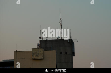 Various antennas on top of a building - Stock Photo