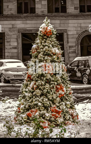 Fir-tree growing outside, covered with the first snow,decorated with Christmas decorations, white balls, red poinsettia and LED lights garlands - Stock Photo