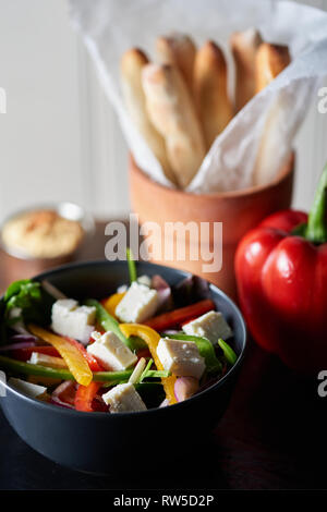 Shallow depth of field shot of plated food. Healthy Greek salad with cheese and brightly coloured peppers. - Stock Photo