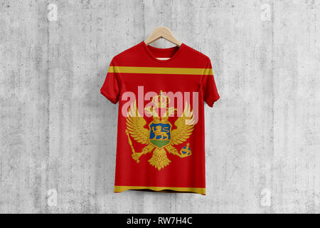 Montenegro flag T-shirt on hanger, Montenegrin team uniform design idea for garment production. National wear. - Stock Photo