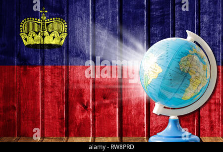 Globe with a world map on a wooden background with the image of the flag of Liechtenstein. The concept of travel and leisure abroad. - Stock Photo