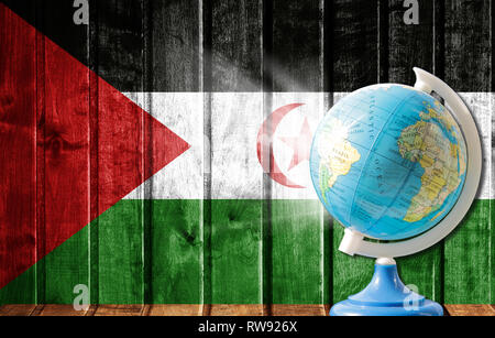 Globe with a world map on a wooden background with the image of the flag of Western Sahara. The concept of travel and leisure abroad. - Stock Photo