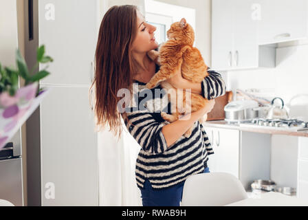 Young woman playing with cat in kitchen at home. Girl holding and hugging ginger cat. Happy master having fun with her pet - Stock Photo