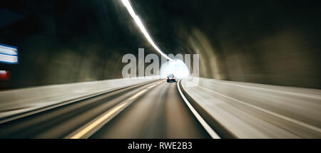 A motion blurred car traveling through a road tunnel. - Stock Photo