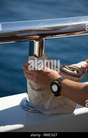 Close up of crew member's hands polishing railing on Superyacht - Stock Photo