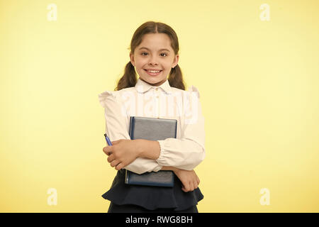 Happy schoolgirl hold book on yellow background. Little girl smile with textbook and pen. Confident in her knowledge. Dedicated to study. Adorable bookworm. Back to school. - Stock Photo