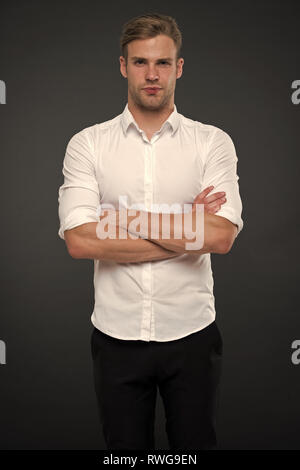 I am here to help you. Man shop consultant looks confident and hospitable. Man calm face posing confidently with folded arms grey background. Guy with bristle ready to help you in shop. - Stock Photo
