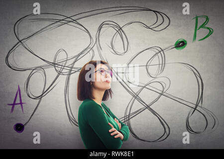 Confident woman arms crossed wearing glasses looking up trying to find the correct way from one point A to another B. Solving problem, search for solu - Stock Photo