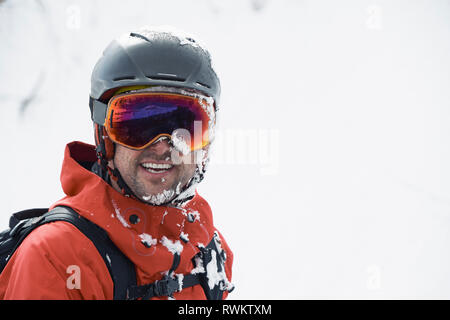 Male skier in ski helmet and goggles with frosty beard, portrait, Alpe-d'Huez, Rhone-Alpes, France - Stock Photo