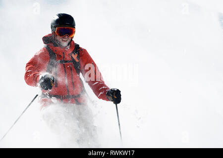 Male skier covered in powder snow on mountainside Alpe-d'Huez, Rhone-Alpes, France - Stock Photo