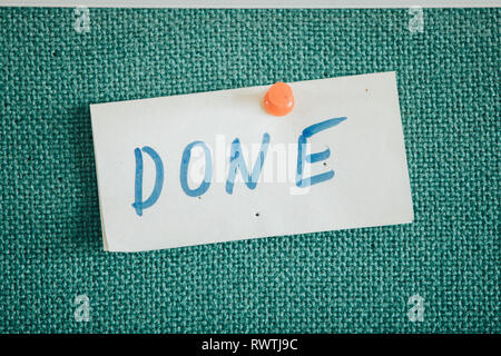 'Done' sign written on a paper with orange pin - Stock Photo