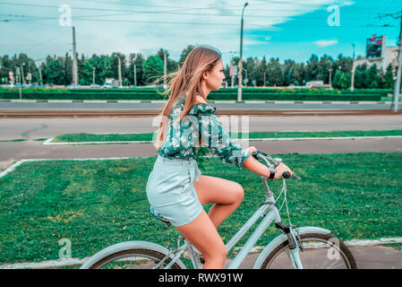 A girl rides a bicycle in the summer in the city on the background of green grass. Returns from a bike run in the weekend in fresh air, fitness in the - Stock Photo