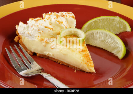 Closeup of key lime pie with fresh lime wedges - Stock Photo