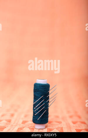 Picture of sewing thread and needles on the orange cloth. - Stock Photo