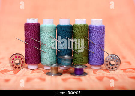 Picture of multicolored thread, bobbins and needles on the orange cloth. - Stock Photo