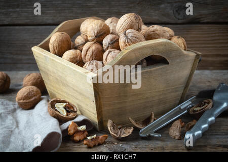 Walnuts in a wooden crate and nutcracker on wooden table. - Stock Photo