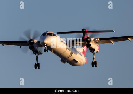 QantasLink (Sunstate airlines) Bombardier DHC-8-402 twin engine turboprop regional airliner on approach to land at Adelaide Airport. - Stock Photo