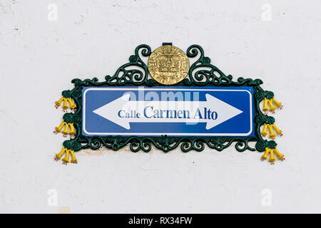 Traditional street sign decorated with Inca motifs and the national flower of Peru called Cantuta (Cusco, Peru) - Stock Photo