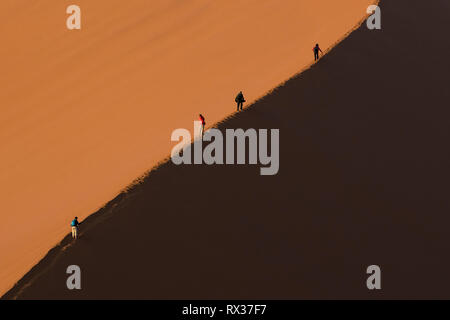 Tourists climb a large red sand dune in Sossusvlei, Namibia. - Stock Photo