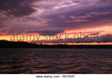 Island under threatening gray and red flaming clouds. Raging sea at sunset with a dark colorful sky - Stock Photo