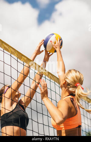 Beach volleyball players at the net - Stock Photo