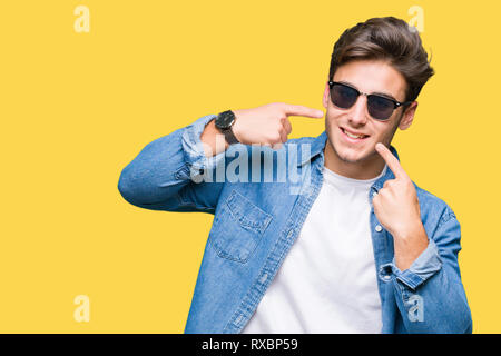 Young handsome man wearing sunglasses over isolated background smiling confident showing and pointing with fingers teeth and mouth. Health concept. - Stock Photo