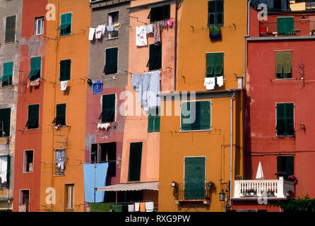 Multicolored facades marked by windows, shutters, balconies, and laundry hung out to dry decorate the vertical dwellings that overlook the boat harbor at Portovenere, Italy. Strong sunshine along the Mediterranean seacoast is a cause for frequent repainting of the exterior walls of these attached residences. This medieval fishing village on the Italian Riviera is among the most picturesque but lesser-known tourist towns in the Liguria region. - Stock Photo
