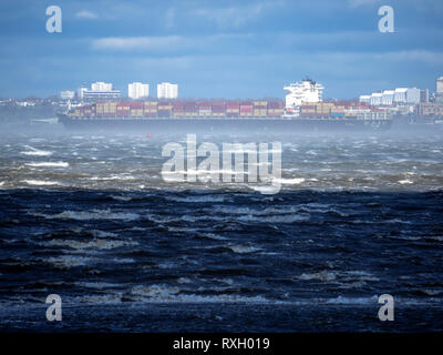 Sheerness, Kent, UK. 10th March, 2019. UK Weather: gale force winds with gusts up to Storm Force 11 (69mph at 10am) have been recorded locally in Sheerness, Kent this morning. Container ship 'CONTI COURAGE' battles through the storm in the Thames Estuary as it passes the end of Southend on sea pier. Credit: James Bell/Alamy Live News - Stock Photo