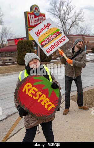 Ypsilanti, Michigan USA. 9th Mar 2019.  Members of the Coalition of Immokalee Workers and their supporters rally at a Wendy's fast food restaurant, asking the company to pay a penny a pound more for the Florida tomatoes it buys. The additional penny would go to improve wages for Florida farmworkers. The rally was part of a tour, targeting Wendy's stores in several university towns. CIW wants the universities to end their relationships with Wendy's until the chain joins the Fair Food Program. Credit: Jim West/Alamy Live News - Stock Photo