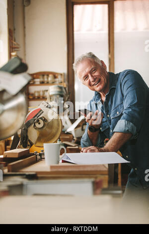 Happy senior man standing by a table in his carpentry workshop with a phone in hand. Mature male carpenter looking at camera and smiling. - Stock Photo