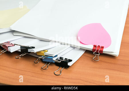 Pile of unfinished documents on office desk, one with heart shape sticker - Stock Photo