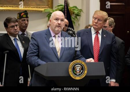 U.S President Donald Trump, right, listens as Thomas Winkel of the Arizona Coalition for Military Families speaks during a signing ceremony for an executive order calling for the Prevents Initiative in the Roosevelt Room of the White House March 5, 2019 in Washington, DC. The initiative calls for a National Roadmap to Empower Veterans and End a National Tragedy of Suicide. - Stock Photo