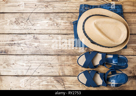 Summer women's clothes. Flat lay fashion photo. Blue jeans, sun hat, blue sandals on wooden background - Stock Photo