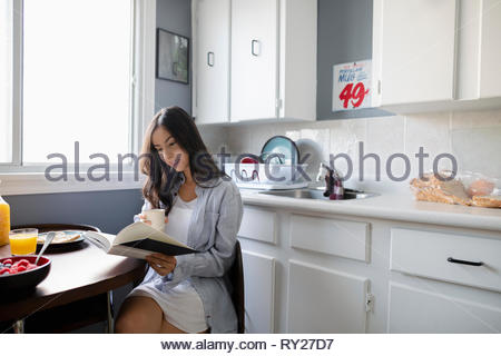 Young Latinx woman drinking coffee and reading book in morning kitchen - Stock Photo