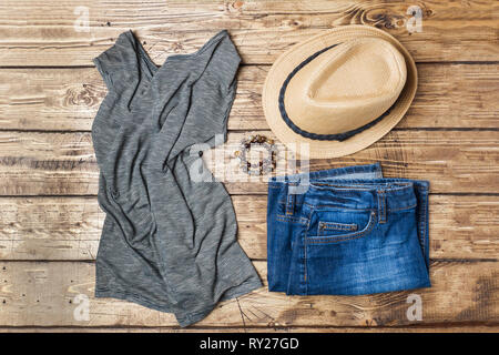 Summer women's clothes. Flat lay fashion photo. Blue jeans, t-shirt, sun hat on wooden background - Stock Photo
