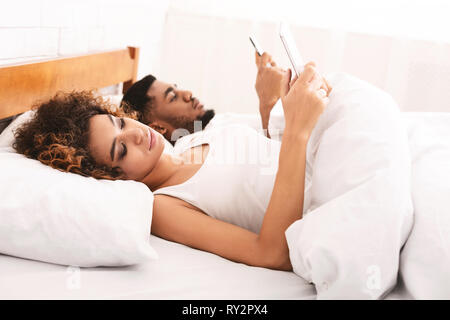 Young couple with mobile phones working from bed - Stock Photo