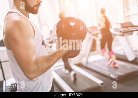 Muscular Bearded man during workout in the gym. Athlete muscular bodybuilder in the gym training biceps with dumbbell. Indoor fitness - Stock Photo