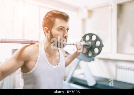 Muscular bearded man during workout in the gym. Bodybuilder doing weight lifting . Close up of young athletic female model trains at the fitness - Stock Photo