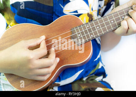 Beautiful girl playing Ukulele on white background. Suitable for music articles or go to Hawaii travel. - Stock Photo
