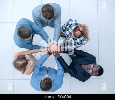 Top view of people putting hands together - Stock Photo