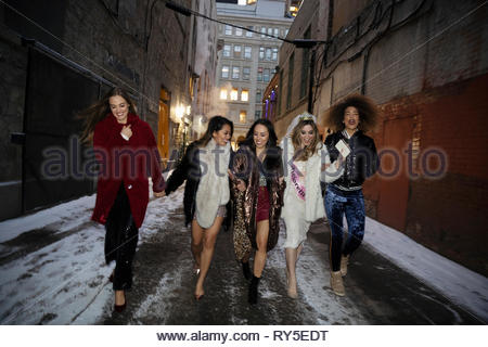 Bachelorette and friends walking along snowy urban alley - Stock Photo