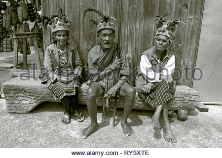 Old Ifugao people with traditional head gear sitting on a bench, Banaue, Luzon, Philippines - Stock Photo